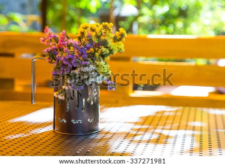 Bunch of dry flowers in a cup, standing on a table in the summer. The cup depicted notes. - stock photo