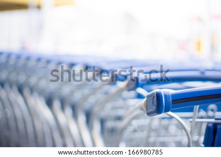 Bunch of empty blue shopping cart at supermarket entrance