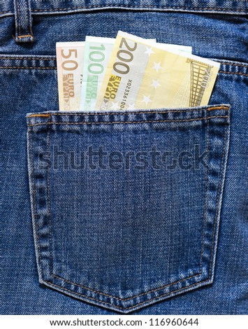 Bunch of Euro banknotes in the back pocket of a blue jeans.