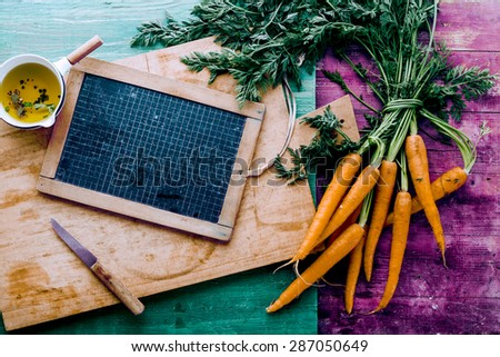 Bunch of farm fresh healthy carrots with a blank vintage school slate on a wooden chopping board with seasoned oil, overhead view on a colored shabby chic background - stock photo