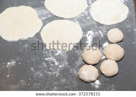 Bunch of flour dough and buns on table - stock photo