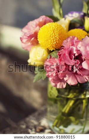 Bunch of flowers in a glass jar - stock photo
