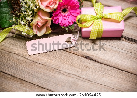 Bunch of flowers with an empty tag on wooden background - stock photo
