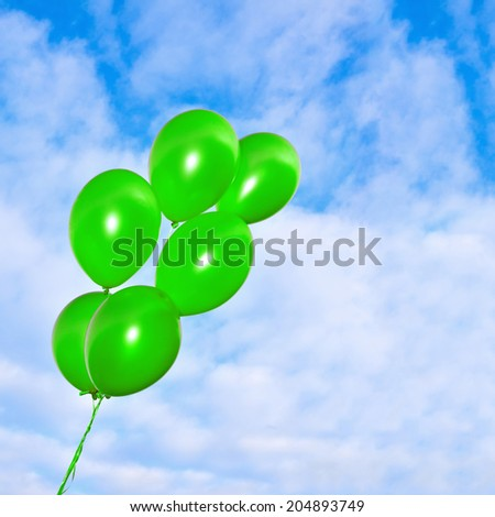 Bunch of flying inflatable golden balloons on the beautiful sky background - stock photo