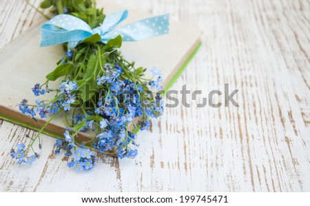 Bunch of forget-me-nots flowers and  old book - stock photo