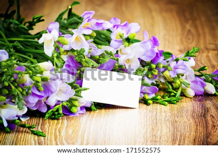 Bunch of freesia flowers with greeting card