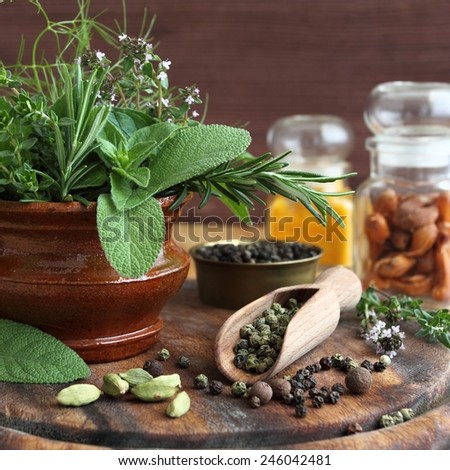 Bunch of fresh aromatic herbs in a ceramic pot and spices. - stock photo