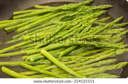 Bunch of fresh asparagus cooking in a pan of hot water - stock photo