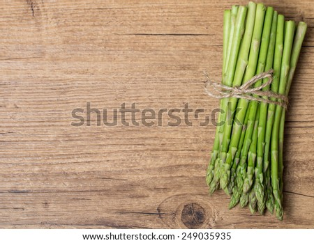 Bunch of fresh asparagus on wooden table - stock photo