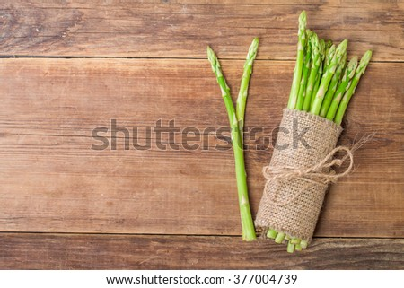 bunch of fresh asparagus stems on brown wooden table. Top view - stock photo