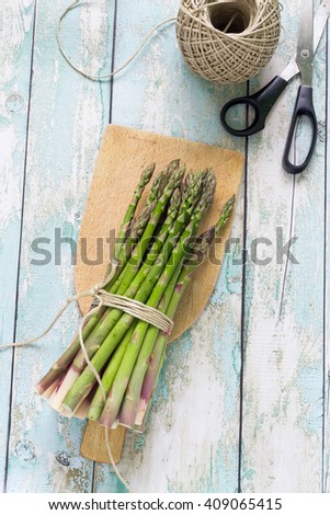 Bunch of fresh asparagus tied on a rustic wooden table with scissors and string. Flat lay image of fresh asparagus vegetables. - stock photo