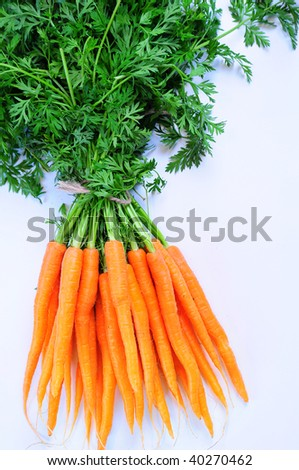 Bunch of fresh baby carrots on white background. - stock photo