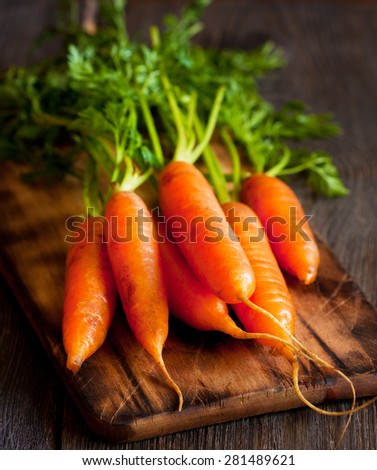 Bunch of fresh carrots  on an old wooden cooking board. - stock photo
