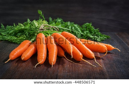 Bunch of fresh carrots vegetables with green leaves on rustic wooden background - stock photo