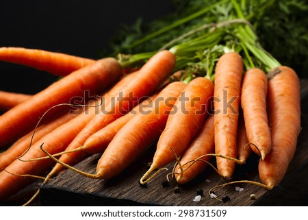 Bunch of fresh carrots with green leaves on wooden cutting board