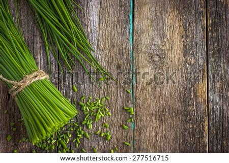 bunch of fresh chives on a wooden cutting board, top view - stock photo