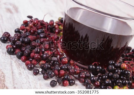 Bunch of fresh elderberry and glass of elderberry juice on old rustic wooden background, healthy nutrition, alternative medicine and therapy - stock photo