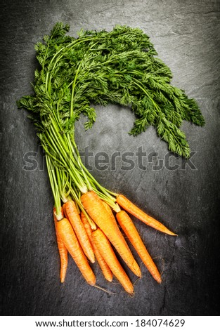 Bunch of fresh farm carrots with their green leaves at a farmers market lying on an old textured slate surface, overhead view - stock photo