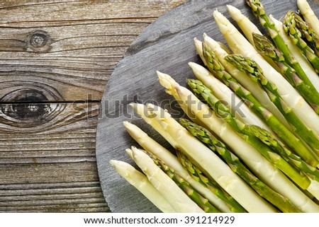 Bunch of fresh green and white asparagus on wooden background, rustic style, copy space - stock photo