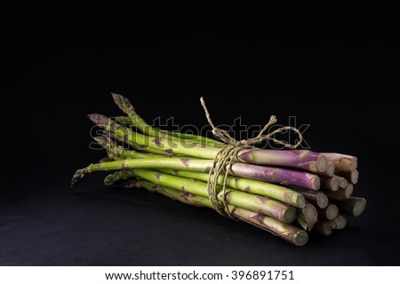 bunch of fresh green asparagus on a dark background, that is changing to black, copy space - stock photo