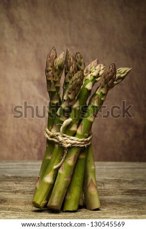 Bunch of fresh green asparagus spears tied with string on a rustic wooden table top - stock photo