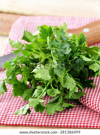 bunch of fresh green organic parsley on a wooden table - stock photo