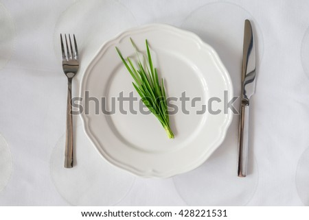 bunch of fresh herbs on an empty plate with knife and fork. Diet concept
