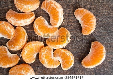 Bunch of fresh juicy mandarin orange cloves full of vitamins on brown wooden surface - stock photo