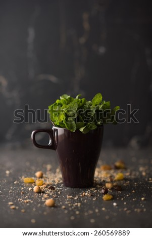 Bunch of fresh mint in cup on rustic stone background - stock photo
