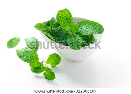 Bunch of fresh mint in white bowl isolated on white background.