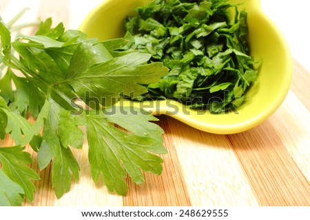 Bunch of fresh natural and green parsley and chopped parsley in background lying on wooden cutting board, concept for healthy eating - stock photo