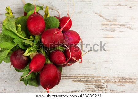 Bunch of fresh radishes on a white, old wooden background with empty space for possible text on the right. Horizontal, flat top view - stock photo