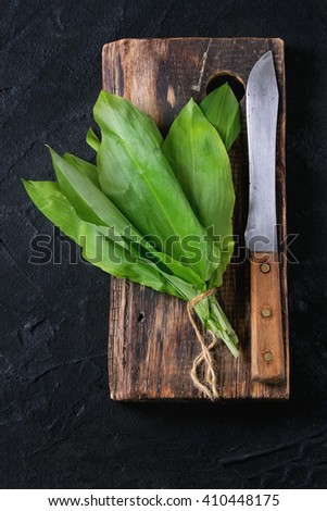 Bunch of fresh ramson on wooden chopping board with vintage knife over black textured background. Top view - stock photo