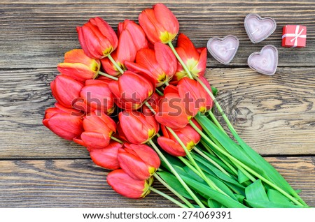 Bunch of fresh red tulips lying alongside a a heart candles for a loved one or sweetheart on Valentines Day or an anniversary, overhead view - stock photo