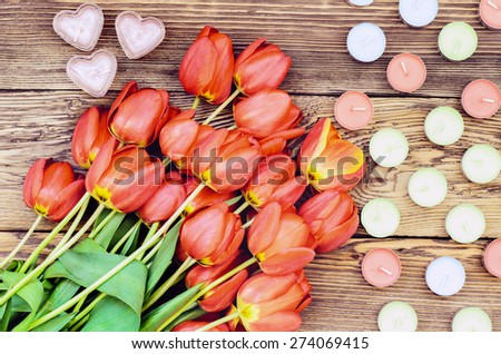 Bunch of fresh red tulips lying alongside a heart candles of colorful candles for a loved one or sweetheart on Valentines Day or an anniversary, overhead view - stock photo