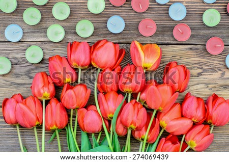 Bunch of fresh red tulips lying alongside of colorful candles on Valentines Day or an anniversary, overhead view - stock photo