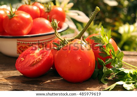 Bunch of fresh ripe tomatoes and half of cut tomato against background tomatoes in bowl and white flowers