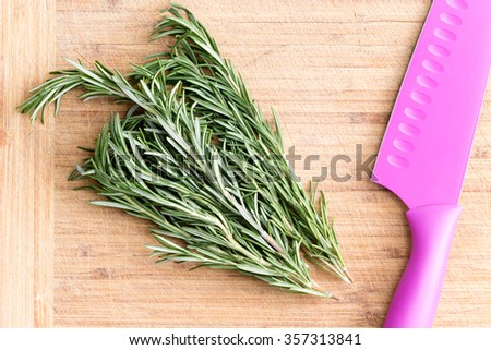 Bunch of fresh rosemary sprigs on a bamboo chopping board with a colorful pink knife ready to be prepared as a flavoring and seasoning or garnish for cooking, overhead view - stock photo