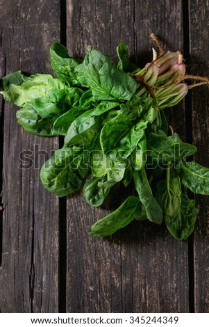 Bunch of fresh spinach with roots over old wooden surface. Dark rustic style. Top view - stock photo