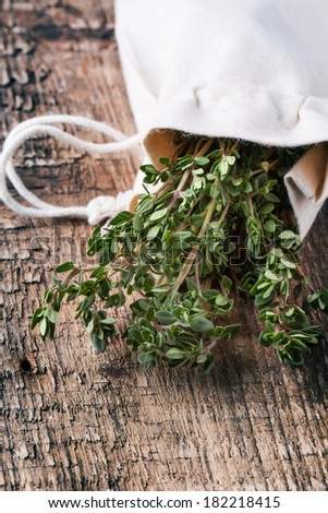 Bunch of fresh thyme in textile bag on wooden table