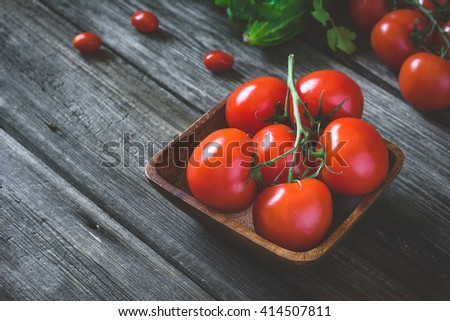 Bunch of fresh tomatoes on vine in wooden bowl on rustic wooden table. Selective focus, toned image - stock photo