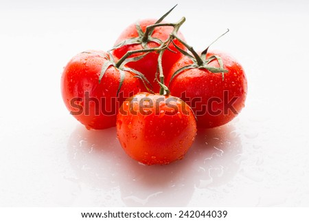 Bunch of fresh tomatoes with water drops - stock photo