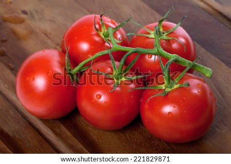 Bunch of fresh tomatoes with water drops on wooden table - stock photo