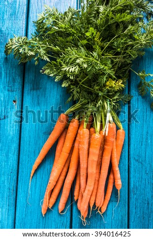 Bunch of fresh vibrant carrots from local market, from above on wooden rustic table - stock photo