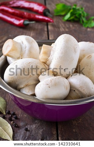 Bunch of fresh white mushrooms in the purple bowl on a wooden background - stock photo