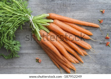Bunch of freshly picked carrots on wood - stock photo