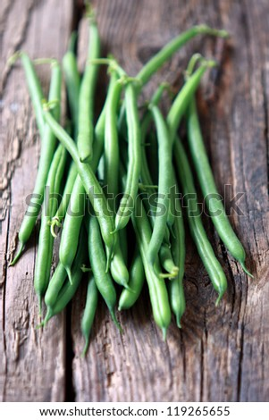 Bunch of freshly picked green beans on a wooden surface. - stock photo