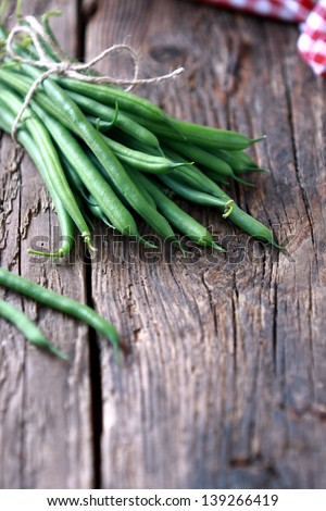 Bunch of freshly picked green beans on a wooden surface. Rustic take. - stock photo