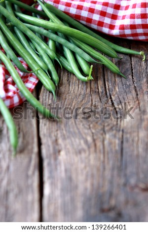 Bunch of freshly picked green beans on a wooden surface. Rustic take. Copy space - stock photo