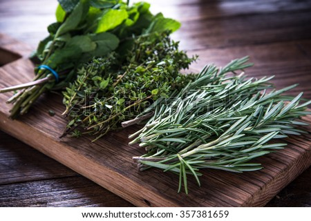 bunch of garden fresh herbs on wooden board from above - stock photo